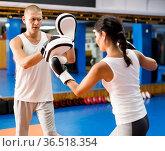 Man holding focus mitts during self defence training with woman. Стоковое фото, фотограф Яков Филимонов / Фотобанк Лори