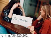 Hidden depression concept. Sad woman with psychologist holding white... Стоковое фото, фотограф Zoonar.com/Max / easy Fotostock / Фотобанк Лори