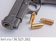 Gold bullets and gun on aluminium background. Стоковое фото, фотограф Zoonar.com/Jiri Plistil / easy Fotostock / Фотобанк Лори