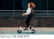 Young woman with electric scooter at the city. Стоковое фото, фотограф Zoonar.com/Max / easy Fotostock / Фотобанк Лори