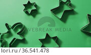 Angel, gingerbread man and star shaped cookie cutters and copy space on green background. Стоковое видео, агентство Wavebreak Media / Фотобанк Лори