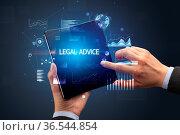 Businessman holding a foldable smartphone with LEGAL ADVICE inscription... Стоковое фото, фотограф Zoonar.com/rancz / easy Fotostock / Фотобанк Лори