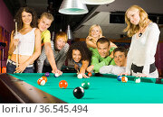 Large group of teenagers standing at pool table. Smiling and looking... Стоковое фото, фотограф Zoonar.com/Tomasz Trojanowski / easy Fotostock / Фотобанк Лори