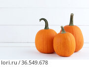 Three pumpkins on white wood. Стоковое фото, фотограф Иван Михайлов / Фотобанк Лори