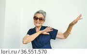Female portrait of beautiful old grandmother with grey hair and face with wrinkles is dancing on white background, mothers day, happy retirement. Стоковое видео, видеограф Ольга Балынская / Фотобанк Лори