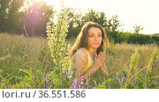 Pretty young girl is sitting in the middle of the field with flowers during summer time and sneezing, hypersensitivity, asthma, or allergy concept. Стоковое видео, видеограф Ольга Балынская / Фотобанк Лори