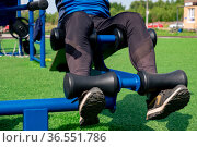Legs of a person, shakes her press using an outdoor exercise machine abdominal bench. Стоковое фото, фотограф Евгений Харитонов / Фотобанк Лори