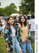 Two girl friends hang out and joke around in the midway at the county... Стоковое фото, фотограф Lori Epstein / age Fotostock / Фотобанк Лори