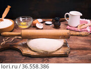 Yeast dough from white flour and a wooden rolling pin on a brown board. Стоковое фото, фотограф Zoonar.com/Danko Natalya / easy Fotostock / Фотобанк Лори