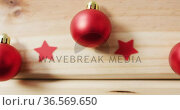Video of red baubles and stars on pale wooden background. Стоковое видео, агентство Wavebreak Media / Фотобанк Лори