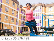 Young woman shakes her triceps using street chest press weight machine in the city yard. Стоковое фото, фотограф Евгений Харитонов / Фотобанк Лори