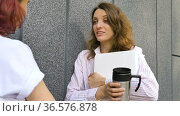 Two successful businesswomen are talking about a the project while standing near the wall outside with a laptop during a break from work. Стоковое видео, видеограф Ольга Балынская / Фотобанк Лори