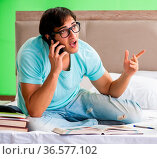 Student preparing for exams at home in bedroom sitting on the bed. Стоковое фото, фотограф Zoonar.com/Elnur Amikishiyev / easy Fotostock / Фотобанк Лори