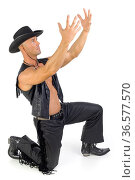 Handsome man kneeling in cowboy costume. Holding hands up in prayer... Стоковое фото, фотограф Zoonar.com/Tomasz Trojanowski / easy Fotostock / Фотобанк Лори