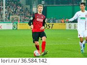 Immanuel Höhn (Freiburg) mit Ball vs Dong-Won JI (Augsburg), DFB-... Стоковое фото, фотограф Zoonar.com/Joachim Hahne / age Fotostock / Фотобанк Лори