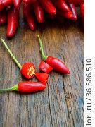 Chilischoten ganz und aufgeschnitten auf Holztisch. Стоковое фото, фотограф Zoonar.com/Thomas Klee / easy Fotostock / Фотобанк Лори