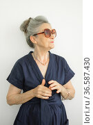 Indoors portrait of beautiful old grandmother with grey hair and fashionable eyeglasses wearing dark blue dress on white background, mothers day, happy retirement. Стоковое фото, фотограф Ольга Балынская / Фотобанк Лори