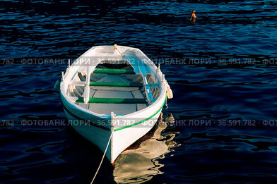 Fishing white wooden boat with oars on the blue water of the Bay of...