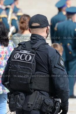 Сотрудники федеральной службы охраны обеспечивают безопасность во время церемонии развода конных и пеших караулов Президентского полка на Соборной площади Московского Кремля