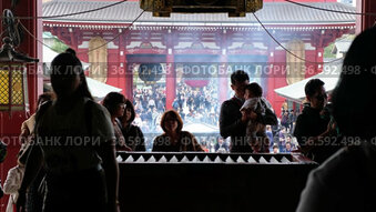 Video of people praying at the entrance to the main hall in front of offering box (saisen) under the great red lantern (akachochin). Sensoji Kannon temple in Asakusa.
