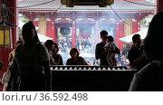 Video of people praying at the entrance to the main hall in front of offering box (saisen) under the great red lantern (akachochin). Sensoji Kannon temple in Asakusa. Редакционное видео, видеограф Serg Zastavkin / Фотобанк Лори