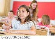 Smiling tween schoolgirl writing in workbook at lesson in class. Стоковое фото, фотограф Яков Филимонов / Фотобанк Лори