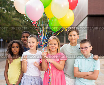 Cheerful happy tween children with colorful balloons on city street