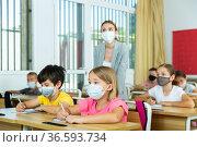 School boy and girl in face masks listening to teacher at lesson in primary school. Стоковое фото, фотограф Яков Филимонов / Фотобанк Лори