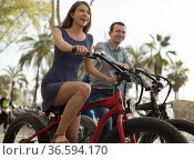 couple guy with a girl ride bicycles with thick wheels in the summer along the promenade. Стоковое фото, фотограф Татьяна Яцевич / Фотобанк Лори