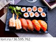 Various sushi served on black plate. Japanese food. Стоковое фото, фотограф Яков Филимонов / Фотобанк Лори
