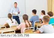 Teacher conducting lesson for teenage schoolchildren in classroom. Стоковое фото, фотограф Яков Филимонов / Фотобанк Лори