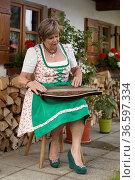 Seniorin im Dirndlkleid sitz zitherspielend vor ihrem alten Bauernhaus. Стоковое фото, фотограф Zoonar.com/Eder Christa / age Fotostock / Фотобанк Лори