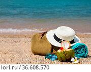 Straw hat, sunglasses, beach towel with beach bag and coconut cocktail... Стоковое фото, фотограф Zoonar.com/Dasha Petrenko / easy Fotostock / Фотобанк Лори