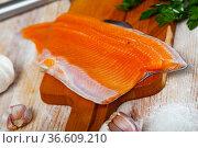 Trout fillet on cutting board with garlic and parsley. Стоковое фото, фотограф Яков Филимонов / Фотобанк Лори