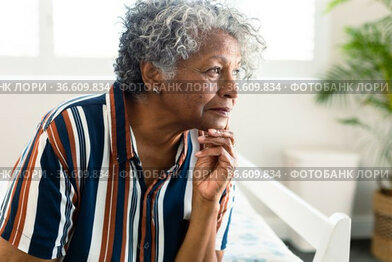 Portrait of thoughtful african american senior woman sitting on bed and look into distance
