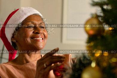 Happy african american senior woman decorating christmas tree