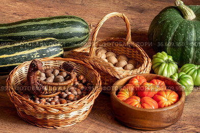 Harvest of fresh tomatoes, pumpkin and courgettes and baskets with hazelnuts and walnuts stacked on the floor