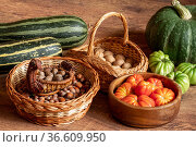 Harvest of fresh tomatoes, pumpkin and courgettes and baskets with hazelnuts and walnuts stacked on the floor. Стоковое фото, фотограф Евгений Харитонов / Фотобанк Лори