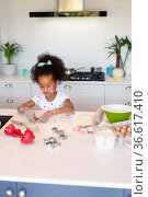 Focused african american messy girl baking in kitchen. Стоковое фото, агентство Wavebreak Media / Фотобанк Лори