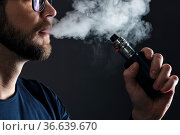 Vaping flavored e-liquid from an electronic cigarette. Стоковое фото, фотограф Zoonar.com/Tomas Anderson / easy Fotostock / Фотобанк Лори