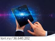 Businessman holding a foldable smartphone with FRAUD PREVENTION inscription... Стоковое фото, фотограф Zoonar.com/rancz / easy Fotostock / Фотобанк Лори