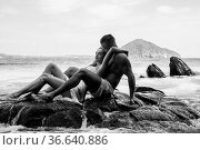 Sensual young couple in white wet clothes sitting on the rock by the... Стоковое фото, фотограф Zoonar.com/Piotr Stryjewski / easy Fotostock / Фотобанк Лори