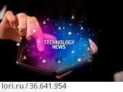 Businessman holding a foldable smartphone with TECHNOLOGY NEWS inscription... Стоковое фото, фотограф Zoonar.com/rancz / easy Fotostock / Фотобанк Лори