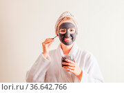 Smiling woman in a towel on the head applying black nourishing mask... Стоковое фото, фотограф Zoonar.com/Oksana Shufrych / easy Fotostock / Фотобанк Лори