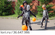 Halloween prepare to collect candy boy in skeleton costume dances on street. Trick or treating. Guising. Jack o lantern. Children in carnival costumes outdoors. Witch and skeletons. orange balloons. Стоковое видео, видеограф Ирина Ткачук / Фотобанк Лори