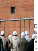 Personen mit Helm und Gummischuhen hinter einem Bauzaun an der Elbphilharmonie... Стоковое фото, фотограф Zoonar.com/Karl Heinz Spremberg / easy Fotostock / Фотобанк Лори