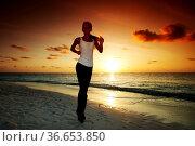 Woman run along the sea coast of sunrise or sunset behind. Стоковое фото, фотограф Zoonar.com/Ivan Mikhaylov / easy Fotostock / Фотобанк Лори