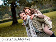 Young caucasian couple in love piggybacking at a park in austria in... Стоковое фото, фотограф Zoonar.com/Daniel Waschnig / easy Fotostock / Фотобанк Лори