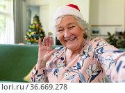 Happy caucasian senior woman wearing santa hat having video call at christmas time. Стоковое фото, агентство Wavebreak Media / Фотобанк Лори
