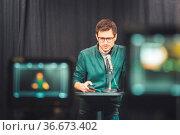 Male journalist in a television studio talks into a microphone, film... Стоковое фото, фотограф Zoonar.com/Patrick Daxenbichler / easy Fotostock / Фотобанк Лори